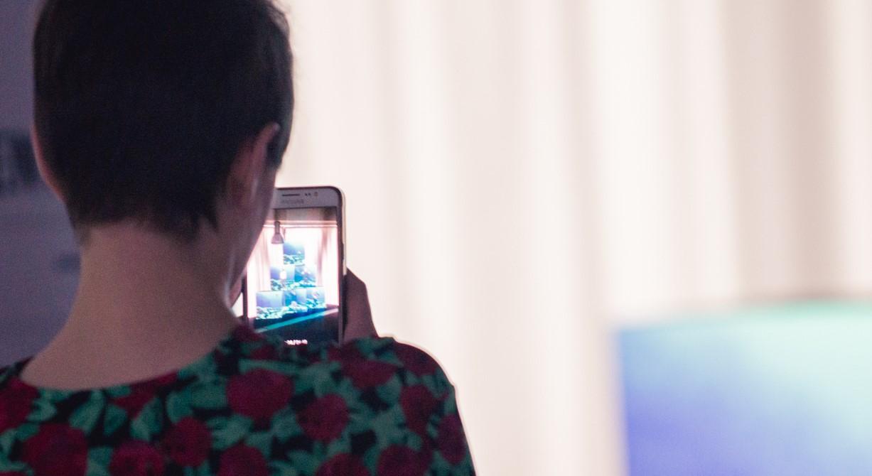 A imaxe correspóndese coa sesión final dun obradoiro de creación dixital, no que unha persoa fotografía co seu móbil o resultado do traballo