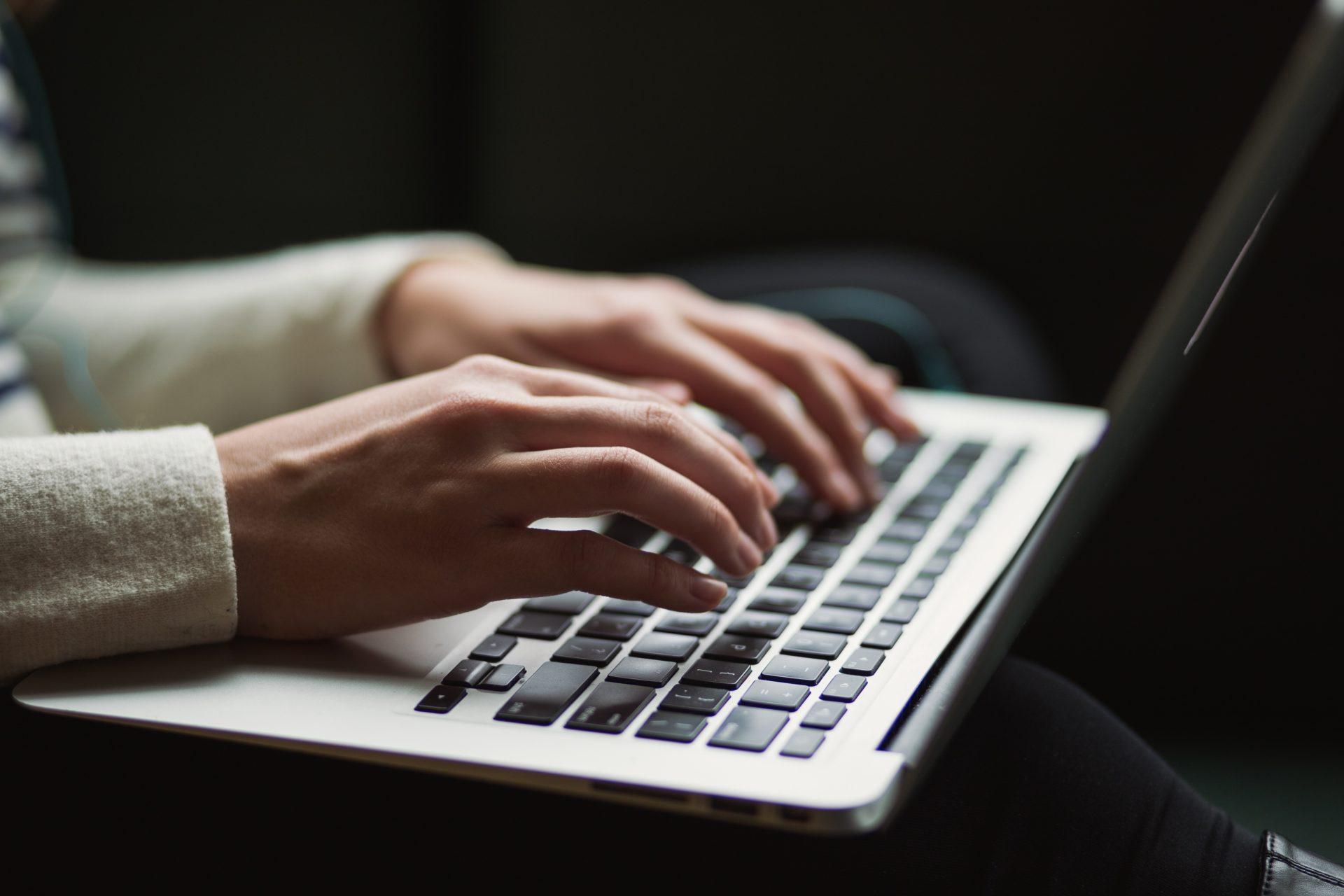 A imaxe amosa as mans dunha rapaza traballando sobre o teclado dun ordenador portátil, en alusión a un dos obradoiros da Normal, que está adicado á creación e coidado dun blog